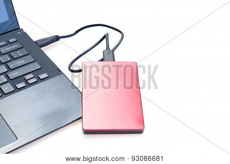 Red external hard disk connected to computer notebook on white
