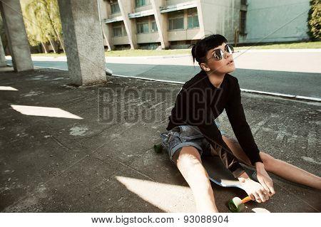 tattooed lady sitting on longboard in backyard