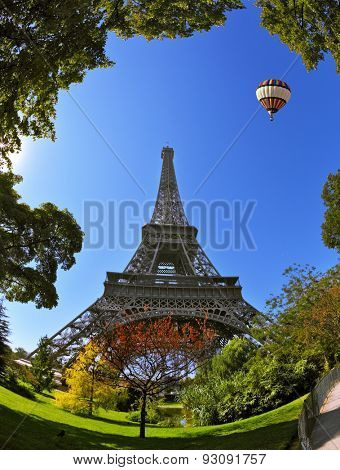 Hugel Eiffel Tower. At the foot of the tower is designed park with paths and pond. In the sky next to the tower floats giant balloon. The picture was taken Fisheye lens.