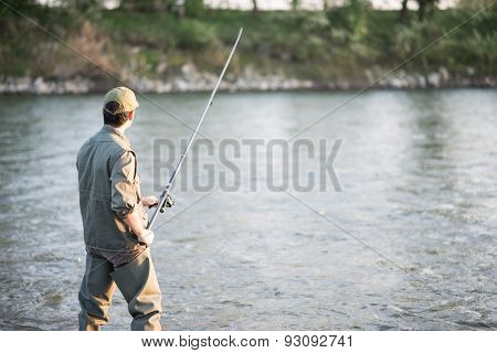 Portrait of a fisherman fishing in a river
