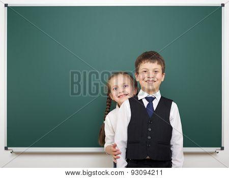 Schoolboy and schoolgirl near school board