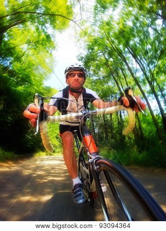 Road bike; male cyclist riding a racing bike downhill. Front view, large copy space. Sport and active life concept.