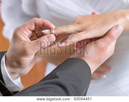 Groom puts a wedding ring on finger of his lovely bride