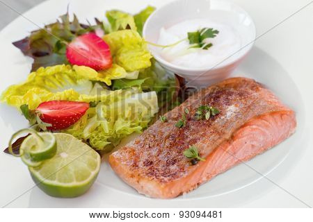 Salmon steak in white dish with vegetables