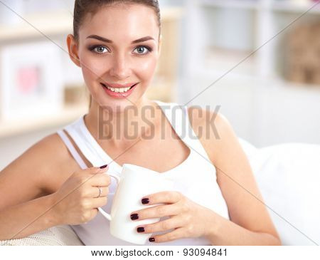 Portrait of oung beautiful woman with a cup on sofa at home .
