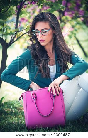 city young woman with fashion accessories. bag and eyeglasses, outdoor in park