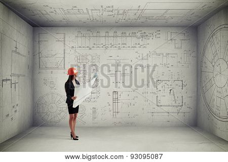 woman in hardhat with blueprint standing in empty room with prints on the walls and ceiling