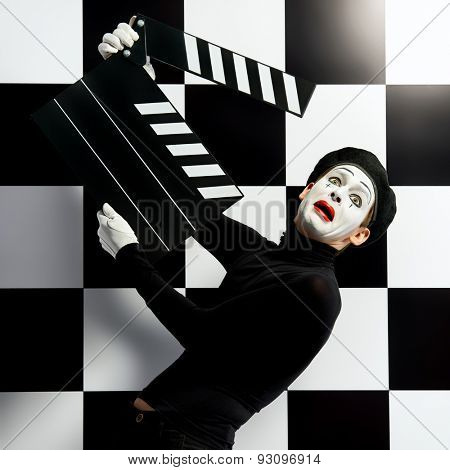 Movie actor and a mime posing with clapper board with different emotions. Chess board background. Cinema industry.