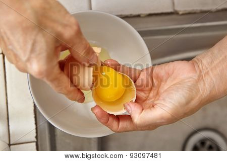 hand separating egg yolk to make bread