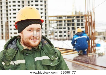 concrete worker. positive foreman in front of carpenters preparing construction formwork for concreting at building area