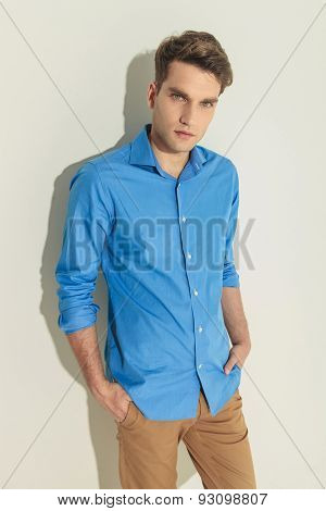 Picture of a young handsome man looking at the camera while holding his hands in pockets.