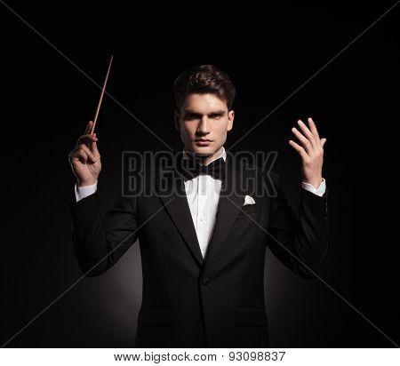 Portrait of a elegant man conducting an orchestra while looking in front.