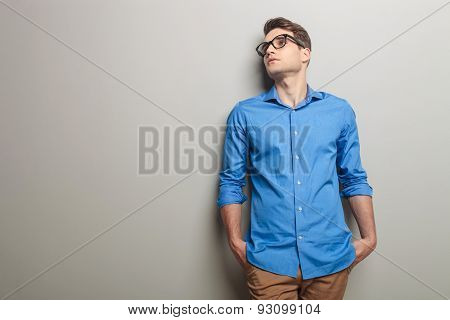 Young casual man holding his hands in pockets while leaning his head on a grey wall.