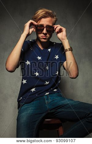 seated fashion man is taking off his sunglasses, studio picture