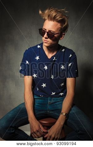 side portrait of a cool fashion man with messy hairstyle looking away from the camera