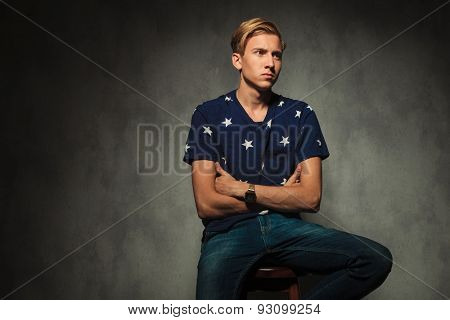 seated fashion man with hands crossed is looking away from the camera to a side