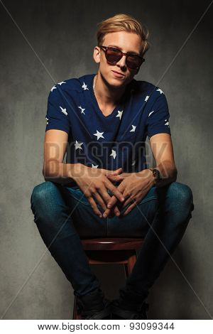 smiling young blond man wearing sunglasses is sitting on a stool