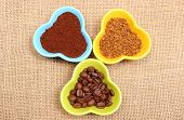 picture of coffee grounds  - Closeup of coffee grains ground coffee and granules of instant coffee in colorful glass cups lying on jute canvas - JPG