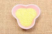 picture of millet  - Closeup of millet groats in pink bowl lying on jute canvas healthy food and healthy nutrition - JPG