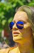 pic of holi  - girl with multicolored face and sunglasses at Holi Festival - JPG