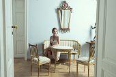 stock photo of aristocrat  - elegant brunette girl in luxury room sitting on vintage sofa with classic hair - JPG