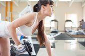 stock photo of bent over  - Female fitness girl exercising indoor in fitness center - JPG