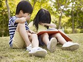 picture of japan girl  - little asian boy and girl sitting on grass laughing while reading a book outdoors in a park - JPG
