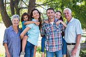 foto of extended family  - Extended family smiling in the park on a sunny day - JPG