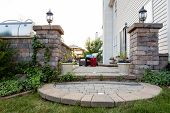 stock photo of flower pot  - Welcoming entrance to an outdoor patio in front of a timber house with a decorative circular step from a green lawn between pillars with lamps to a patio with potted flowers and comfortable furniture - JPG