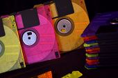 picture of outdated  - Colorful but outdated floppy disks in arrangement against black background - JPG