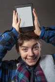 image of lunate  - smiling mad boy holding a tablet computer on his head - JPG