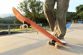 image of skateboard  - skateboarder legs riding on skateboard skatepark ramp - JPG