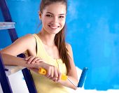 stock photo of wall painting  - Beautiful young woman doing wall painting - JPG