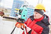 foto of theodolite  - surveyor working with theodolite transit equipment at construction site  - JPG