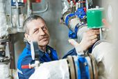 picture of engineer  - repairman plumber engineer of fire engineering system or heating system open the valve equipment in a boiler house - JPG