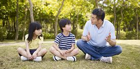 foto of japan girl  - asian father and two children sitting on grass having an interesting conversation outdoors in a park - JPG
