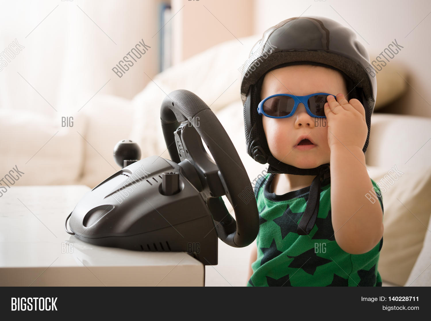 cute little kid boy in a helmet playing with computer steering wheel future driver - Little Kid Pictures