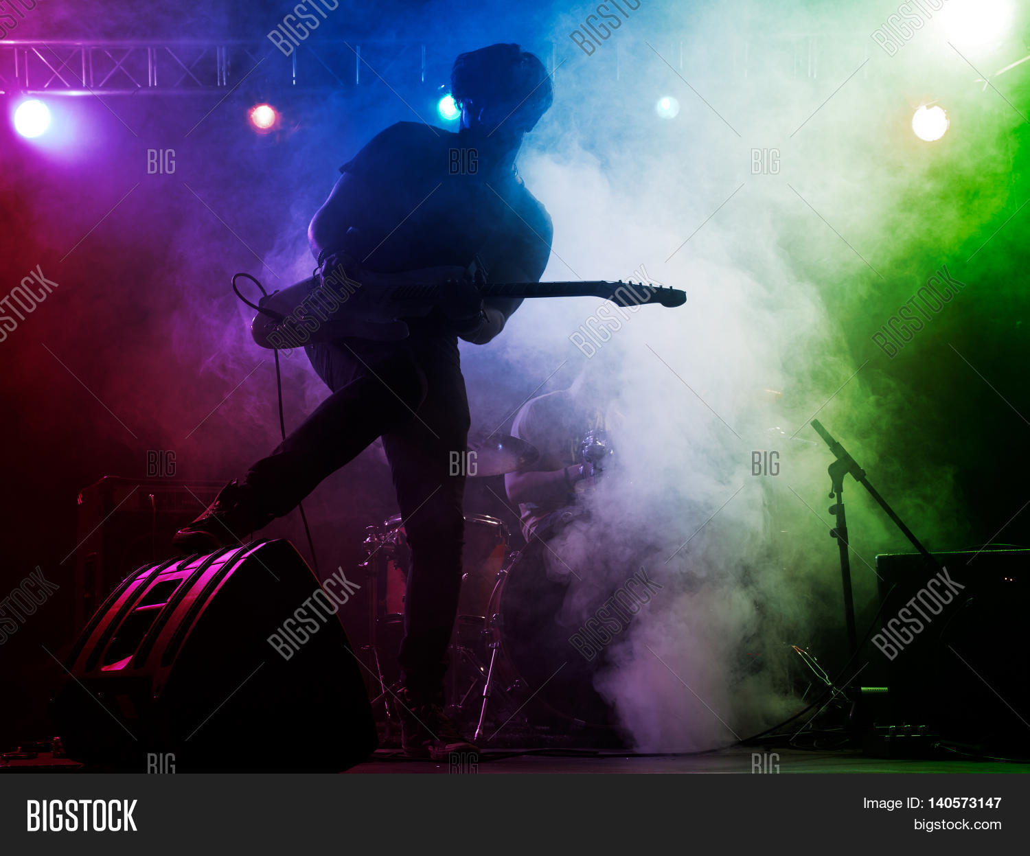 Silhouette of guitar player on stage. Dark background ...