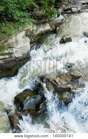 The stream of a mountain river in the Carpathian Mountains, the water flow