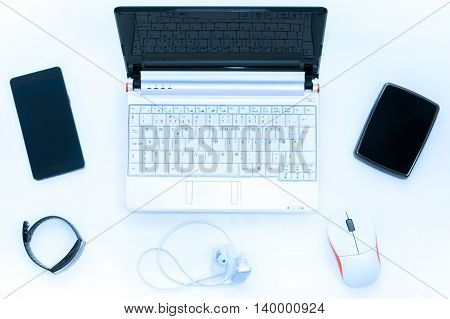 Laptop on white desk with wireless accessories