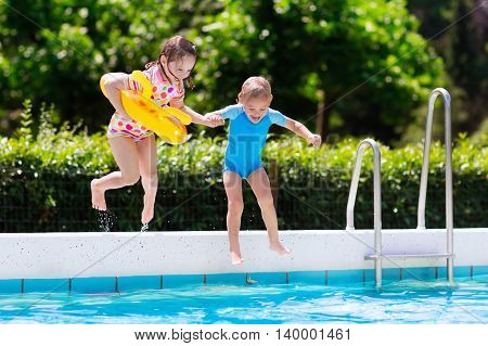 Happy little girl and boy holding hands jumping into outdoor swimming pool in a tropical resort during family summer vacation. Kids learning to swim. Water fun for children. Focus on boy.