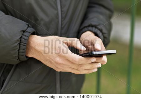 Hand holding and Touch on Black Smartphone outdoors