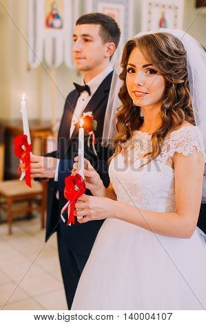 Bride and groom holding lighted candles during the traditional wedding ceremony.