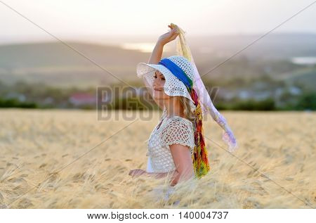 young cheerful woman on golden cereal field in summer