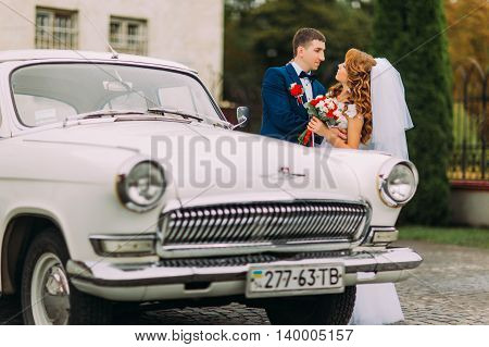 Happy newlywed couple holding each other beside of vintage car.