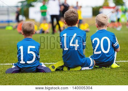 Youth football soccer team sitting together on field and watching soccer match. Young boys as reserve players on bench supporting blue team