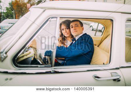 Happy newlywed couple sitting in vintage car. Groom's hands are on handlewheel.