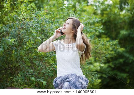 Portrait of beautiful brunette young woman speaking on mobile phone at summer green park