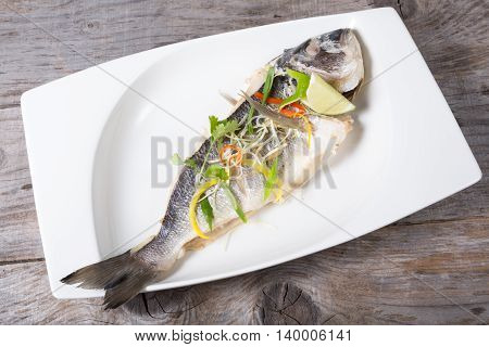 Prepared dorado fish served in a white plate