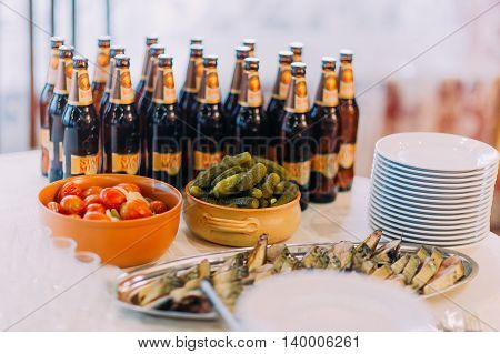 Restaurant table setting with plates, spoons, forks, beer bottles and some food on a background.